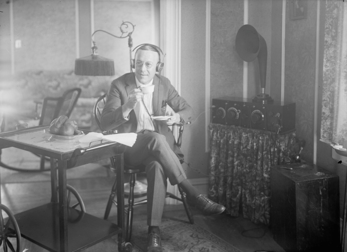 Ernest Hare, US star of Vaudeville, phonograph records, and radio, listens to the radio with headphones. Circa 1921-1925. Bain News Service photograph via Library of Congress website.